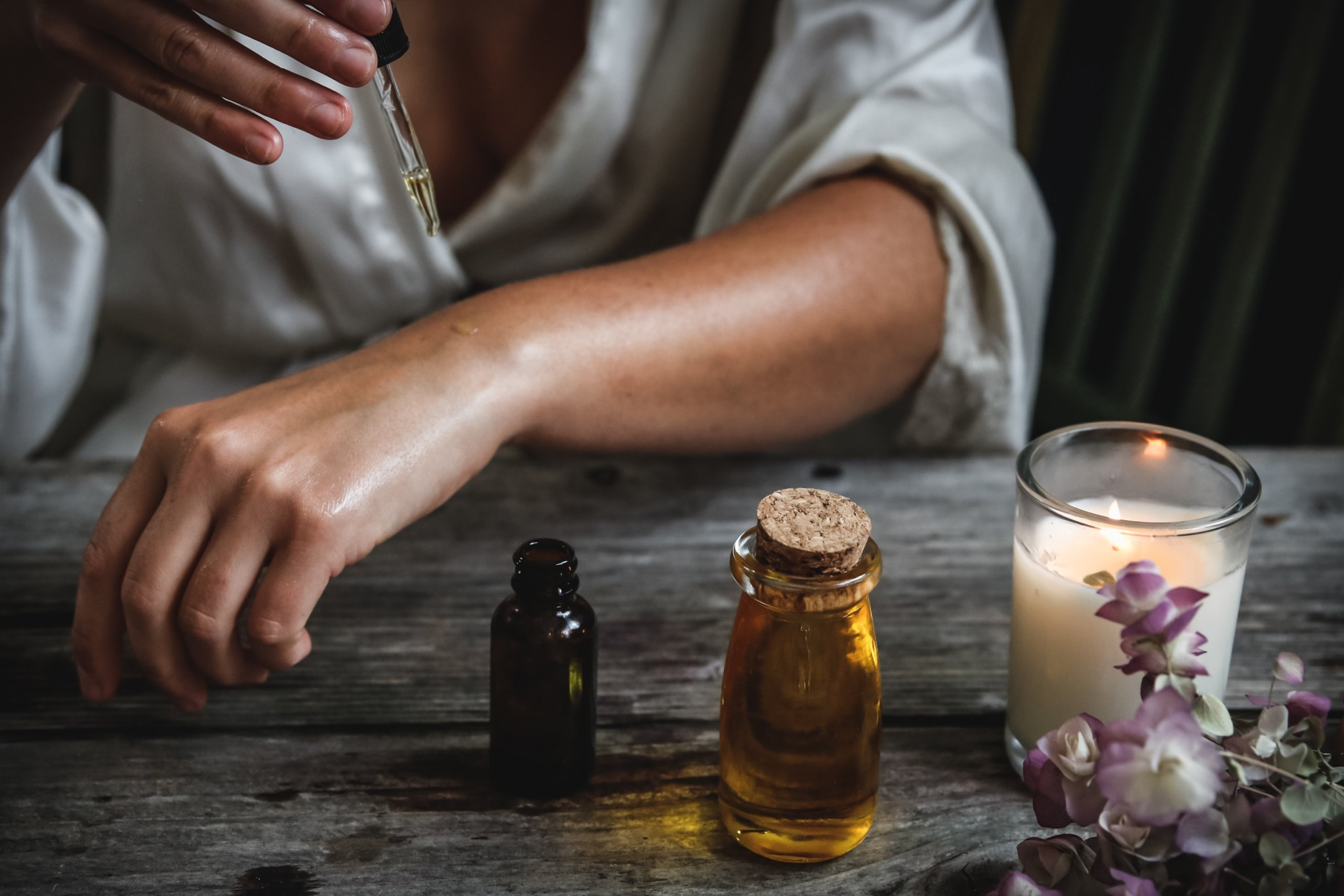 Woman placing oil onto her skin with a dropper with a candle lit next to her
