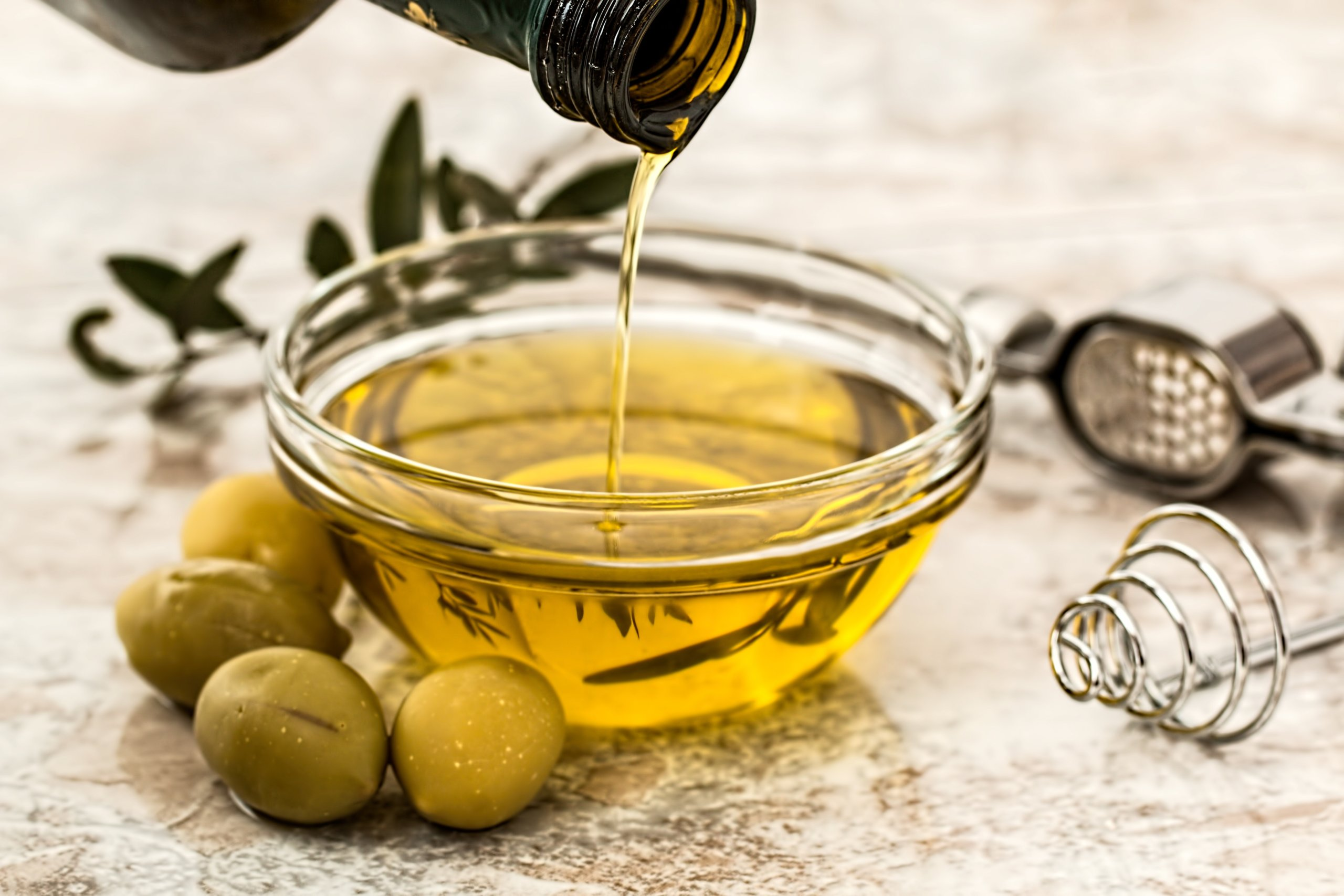 Healthy fat – Olive oil bring poured into small ramekin with olives surrounding the scene